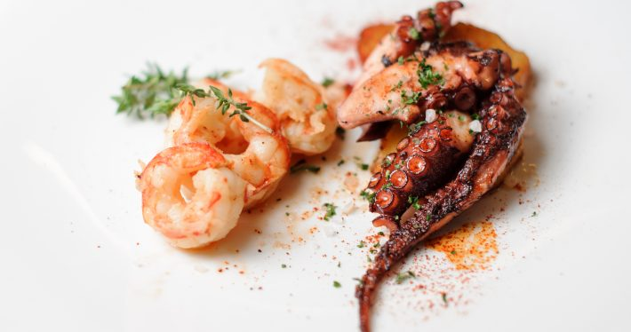 Top view of grilled shrimps and octopus tentacles served on the white plate and decorated with greenery