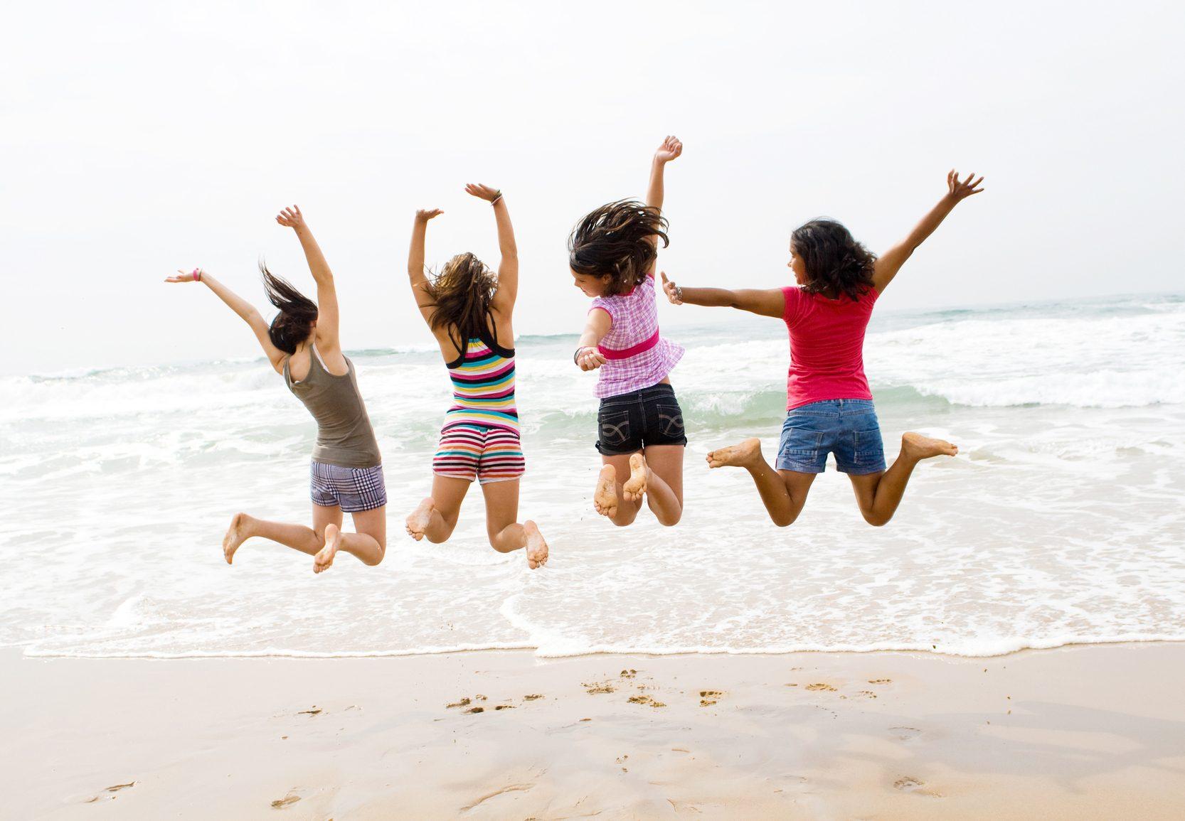 group of teen girls jumping on beach