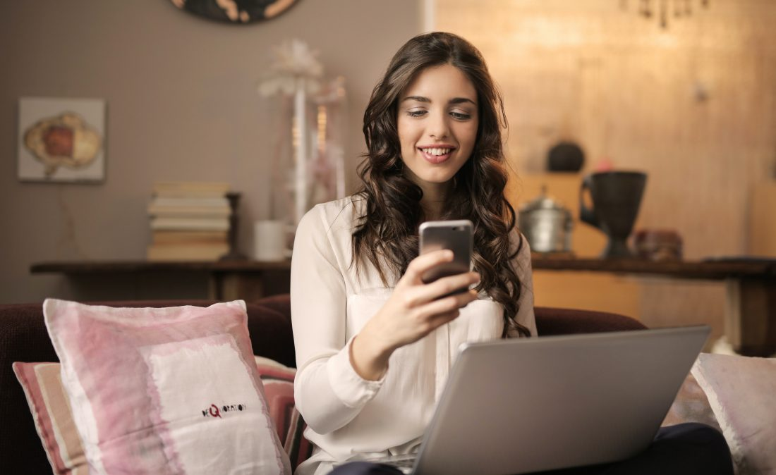 woman-sitting-on-sofa-while-looking-at-phone-with-laptop-on-920382