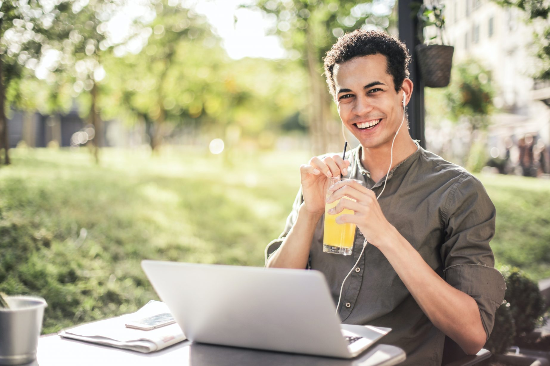 happy-man-sitting-with-laptop-and-juice-in-park-3765030