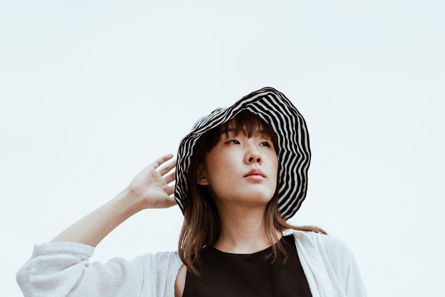 dreamy-asian-woman-in-hat-touching-head-on-blue-background-4429564